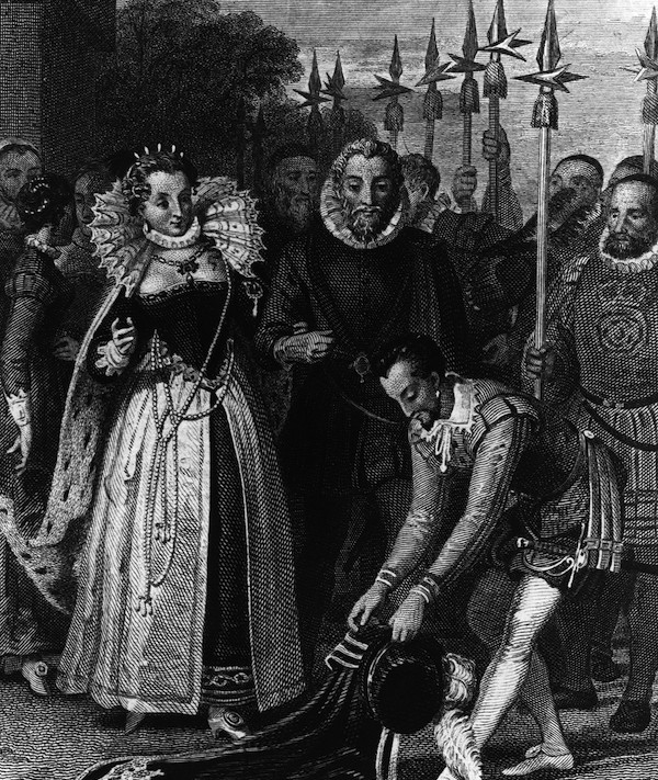 Sir Walter Raleigh (1552 - 1618) lays his cloak across a puddle for Queen Elizabeth I, circa 1600.